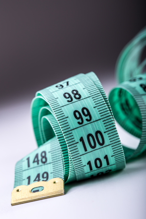tailor tape: Curved measuring tape. Measuring tape of the tailor. Closeup view of Green measuring tape.