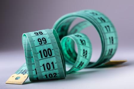 cinta de medir: cinta de medición curvada. cinta de la medida. Vista de detalle de cinta métrica verde. Foto de archivo