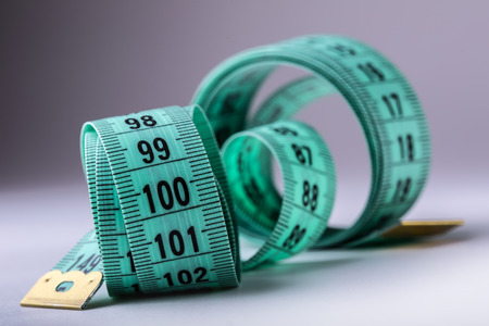 measure: Curved measuring tape. Measuring tape of the tailor. Closeup view of Green measuring tape.