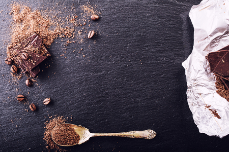 Schokolade. Dunkle Schokolade. Ein paar Würfel aus schwarzer Schokolade. Schokoladenplatten verschüttet aus geriebenen chockolate Pulver. Standard-Bild
