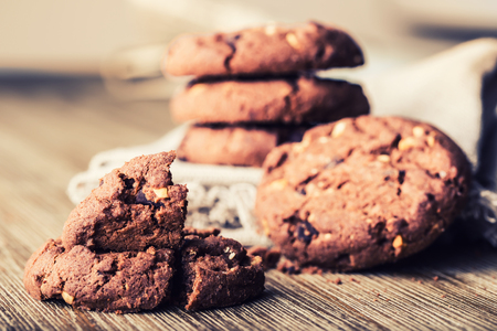 chocolate chip cookies: Chocolate biscuit cookies. Chocolate cookies on white linen napkin on wooden table.
