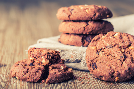 chocolate chips cookies: Chocolate biscuit cookies. Chocolate cookies on white linen napkin on wooden table.