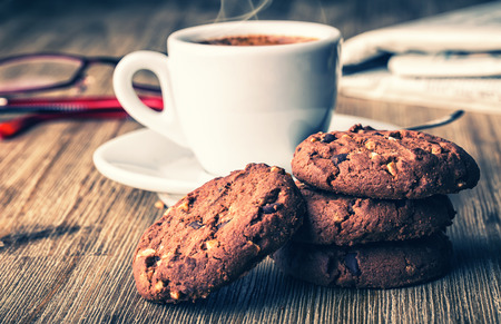 chocolate biscuit: Cup of coffee with biscuit cookies and newspapper. Chocolate biscuit cookies. Chocolate cookies on white linen napkin on wooden table. Coffee break , breakfast.