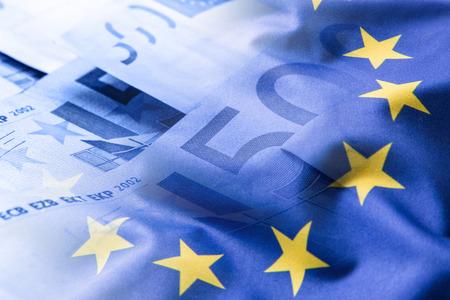 Euro Flagge. Euro Geld. Euro-Währung. Bunte wehenden Flagge der Europäischen Union auf Eurogeldhintergrund.