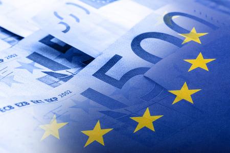 Euro Flagge. Euro Geld. Euro-Währung. Bunte wehenden Flagge der Europäischen Union auf Eurogeldhintergrund. Standard-Bild