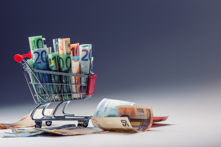 spending full: Shopping trolley full of euro money - banknotes - currency. Symbolic example of spending money in shops, or advantageous purchase in the shopping center. Stock Photo