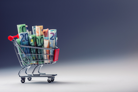 spending money: Shopping trolley full of euro money - banknotes - currency. Symbolic example of spending money in shops, or advantageous purchase in the shopping center. Stock Photo