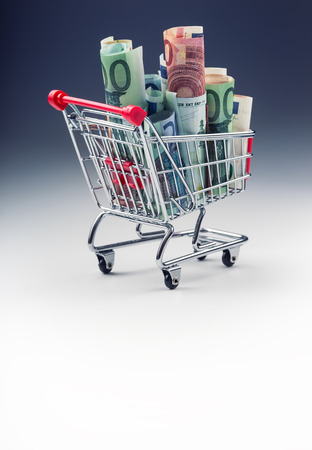 e cash: Shopping trolley full of euro money - banknotes - currency. Symbolic example of spending money in shops, or advantageous purchase in the shopping center. Stock Photo