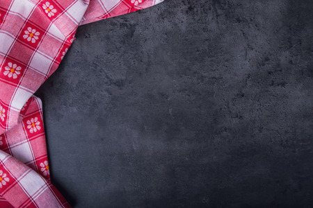 Top view of checkered kitchen tablecloth on granite - concrete - stone background. Free space for your text or products.