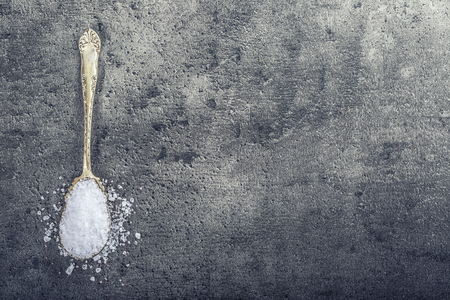 woden: Salt. Coarse grained sea salt on granite - concrete  stone background with vintage spoon and woden bowl. Stock Photo
