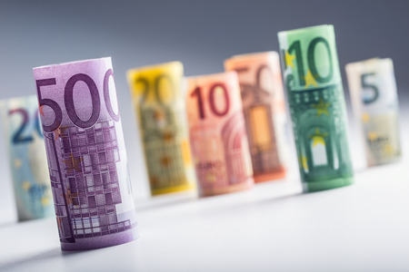 currencies: Several hundred euro banknotes stacked by value. Euro money concept. Rolls Euro  banknotes. Euro currency. Announced cancellation of five hundred euro banknotes. Banknotes stacked on each other in different positions. Toned photo.