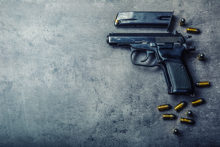 criminal lawyer: 9 mm pistol gun and bullets strewn on the table.