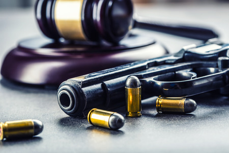 unlawful: Judges hammer gavel. Justice and gun. Justice and the judiciary in the unlawful use of of weapons. Judgment in murder.