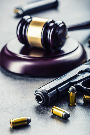 judiciary: Judges hammer gavel. Justice and gun. Justice and the judiciary in the unlawful use of of weapons. Judgment in murder.