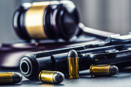 Judge's hammer gavel. Justice and gun. Justice and the judiciary in the unlawful use of of weapons. Judgment in murder.