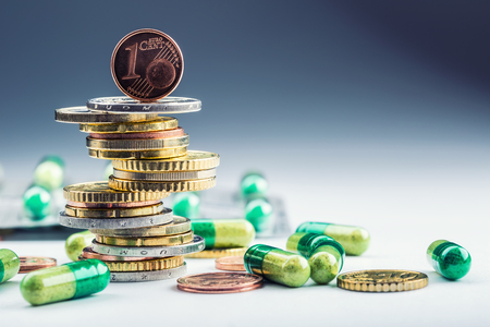 reimbursement: Euro money and medicaments. Euro coins and pills. Coins stacked on each other in different positions and freely pills scattered around. Reimbursement of medicinal products in health care. Stock Photo