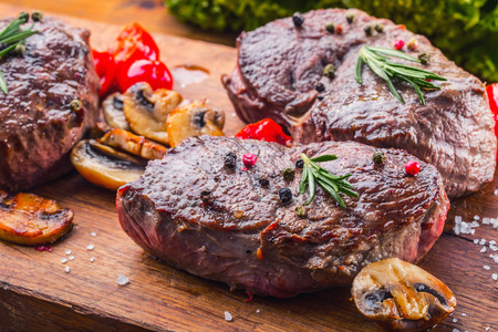 teflon: Grill beef steak. Portions thick beef juicy sirloin steaks on grill teflon pan or old wooden board. Stock Photo