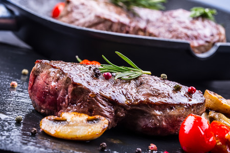 Grill beef steak. Portions thick beef juicy sirloin steaks on grill teflon pan or old wooden board. Stock Photo