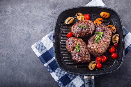 Grill beef steak. Portions thick beef juicy sirloin steaks on grill teflon pan or old wooden board. Banco de Imagens