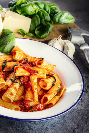nonfat: Pasta. Italian and Mediterrannean cuisine. Pasta Rigatoni with tomato sauce basil leaves garlic and parmesan cheese. An old home kitchen with old kitchen utensils. Stock Photo
