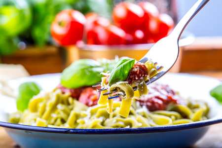 pasta sauce: Pasta. Italian and Mediterranean cuisine. Pasta Fettuccine with tomato sauce basil leaves garlic and parmesan cheese. An old home kitchen with old kitchen utensils. Portion of on a fork pasta with tomato sauce and basil leaves. Stock Photo