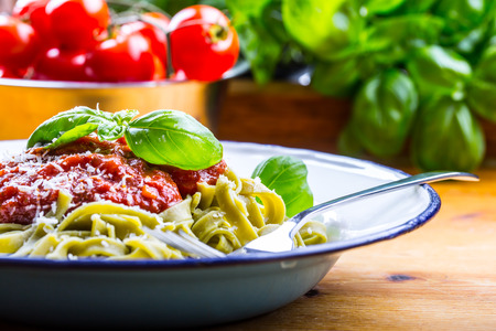 mediterranean home: Pasta. Italian and Mediterranean cuisine. Pasta Fettuccine with tomato sauce basil leaves garlic and parmesan cheese. An old home kitchen with old kitchen utensils. Portion of on a fork pasta with tomato sauce and basil leaves. Stock Photo