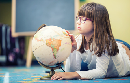 Pretty little student girl studying geography with globe in a childs room.