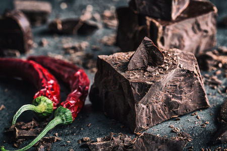 Chocolate and Chili. Black chocolate and chili pepper. Dark chocolate with red chilli pepper. Blocks Bitter chocolate with chili on a spoon spill.