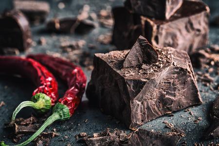 pepe nero: Cioccolato e peperoncino. Cioccolato nero e peperoncino. cioccolato fondente con peperoncino rosso. Blocchi di cioccolato amaro con peperoncino su una fuoriuscita cucchiaio. Archivio Fotografico