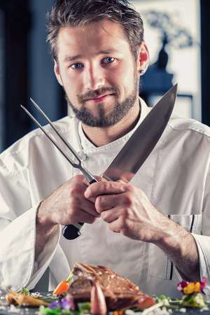 cut up: Chef. Chef funny. Chef with knife and fork arms crossed. Professional chef in a restaurant or hotel prepares or cut up T-bone steak. Chef preparing steak. Cook for their work on catering Stock Photo
