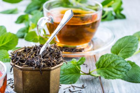 teahouse: Tea. Mint Tea. Herbal tea. Mint leaf. Mint leaves. Tea in a glass cup, mint leaves, dried tea, sliced lime. herbs tea and mint leaves on a slate plate in a restaurant or teahouse tea room.