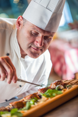 garnishing: Chef. Chef cooking.Chef decorating dish. Chef preparing a meal. Chef in hotel or restaurant kitchen prepares decorating dish with tweezers. Chef cooking, only hands.
