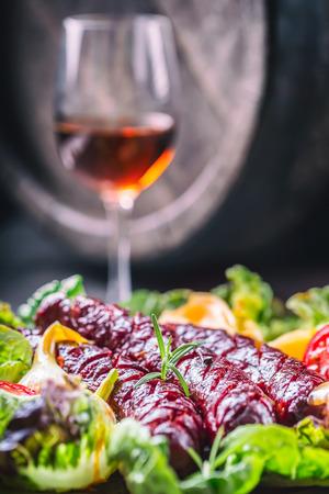salad decoration: Sausage. Roasted chorizo sausage. Roasted spicy sausage chorizo home hotel or restaurant with beer vine brandy cognac whiskey.Vegetable decoration lettuce salad tomato garlic. Toned photo.