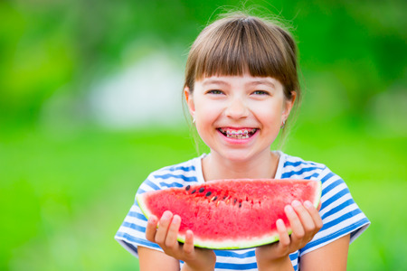 Child eating watermelon. Kids eat fruits in the garden. Pre teen girl in the garden holding a slice of water melon. happy girl kid eating watermelon. Girl kid with gasses and teeth braces. Archivio Fotografico