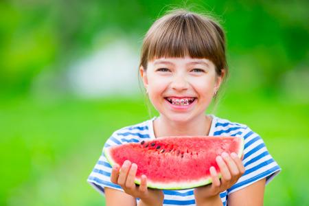 appareil dentaire: Enfant mangeant la pastèque. Les enfants mangent des fruits dans le jardin. Pré fille adolescente dans le jardin tenant une tranche de melon d'eau. heureux jeune fille de manger la pastèque. kid fille avec des gaz et des accolades de dents. Banque d'images