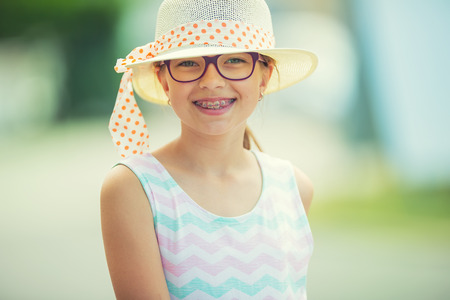 pre teen: Girl.Happy girl teen pre teen. Girl with glasses. Girl with teeth braces. Young cute caucasian blond girl in summer outfit. Stock Photo