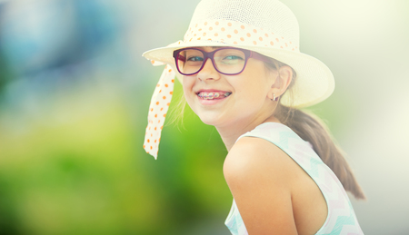 Girl.Happy girl teen pre teen. Girl with glasses. Girl with teeth braces. Young cute caucasian blond girl in summer outfit. Stock Photo