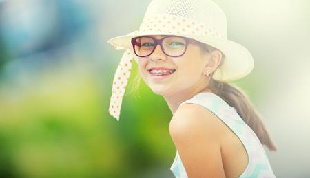 Girl.Happy meisje tiener pre tiener. Meisje met een bril. Meisje met tanden bretels. Schattige jonge blanke blonde meisje in de zomer outfit.