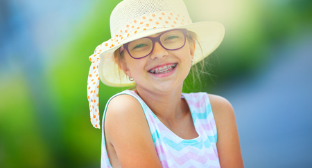 Girl.Happy girl teen pre teen. Girl with glasses. Girl with teeth braces. Young cute caucasian blond girl in summer outfit. Imagens