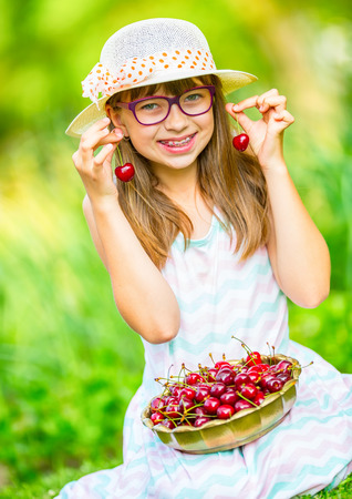cute braces: Child with cherries. Little girl with fresh cherries. Young cute caucasian blond girl wearing teeth braces and glasses. Portrait of a smiling young girl with bowl full of fresh cherries.