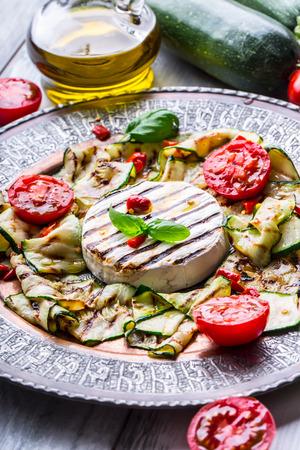 greek cuisine: Grill Brie camembert cheese zucchini with chili pepper and olive oil. Italian mediterranean or greek cuisine. Vegan vegetarian  food. Stock Photo