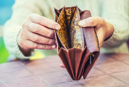Retraité femme tenant les mains portefeuille sans argent. Banque d'images