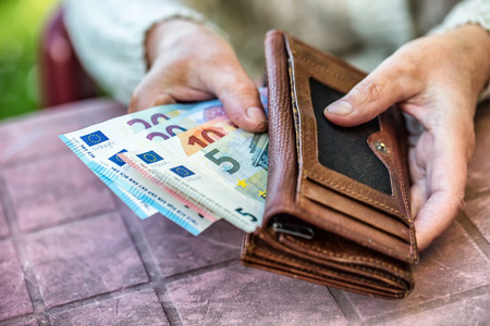 pensioner: Pensioner woman holding in hands wallet with money.