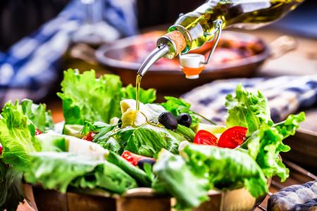 greek cuisine: Vegetable lettuce salad. Olive oil pouring into bowl of salad. Italian Mediterranean or Greek cuisine. Vegetarian vegan food.