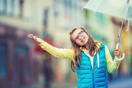 sotto la pioggia: Ritratto di giovane e bella ragazza pre-teen con ombrello sotto la pioggia.