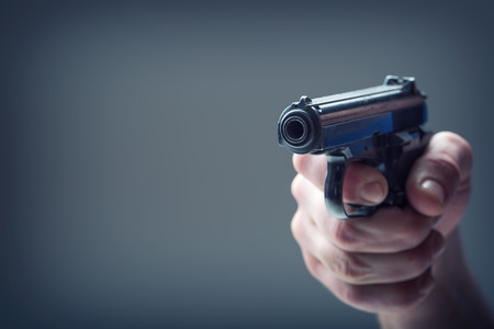 finger on trigger: Weapon gun. Mens hand holding a gun. 9 mm pistol. Stock Photo