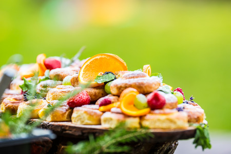 Catering buffet food outdoor. Cakes colorful fresh fruits berries oranges grapes and herb decorations.
