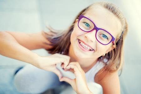 Улыбка маленькая девочка в фигурные скобки и очки, показывая сердце с руками.