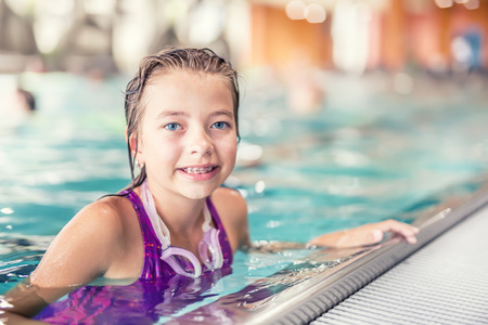 Portrait of a cute young girl with goggles in swimming pool. Swimming training.