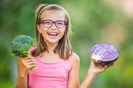 Funny cute girl holding in hands red cabbage and broccoli. Blurred background in garden. Pre-teen young girl with glasses and teeth braces.